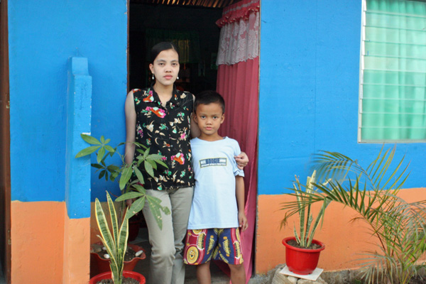 Glenda and her son, standing in from of her new GK house